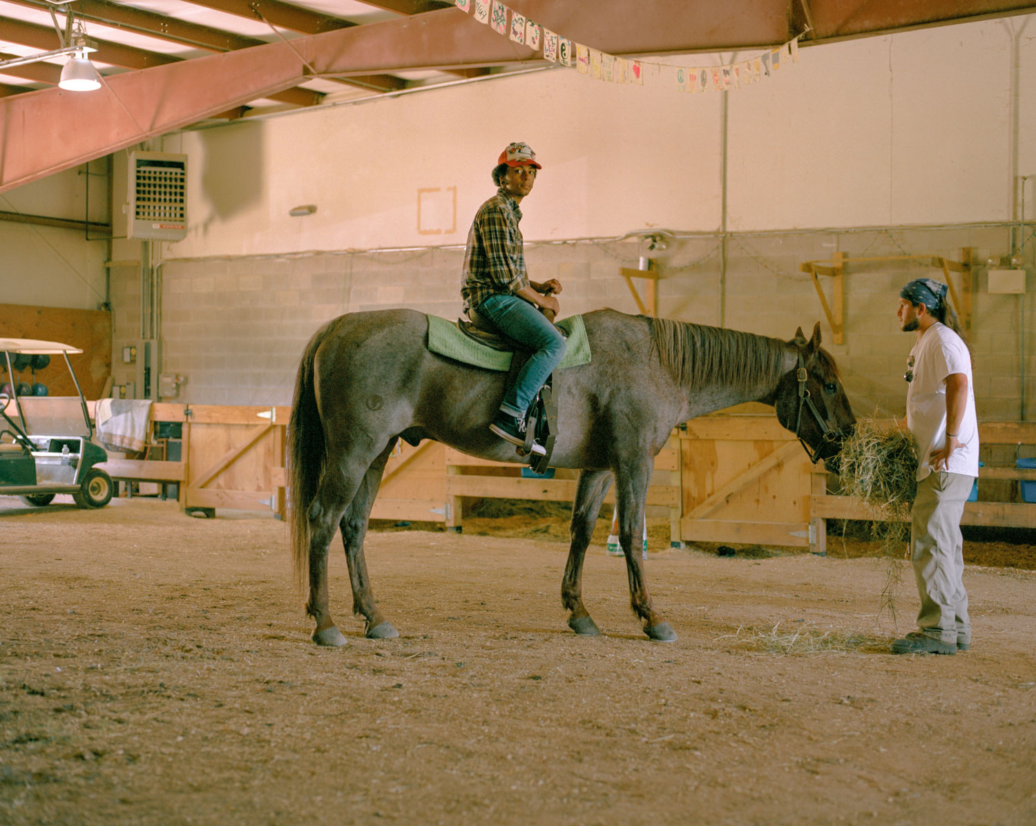 Nikkita, center, and Jay, right, tend to the horses at Hope Farm's stable.